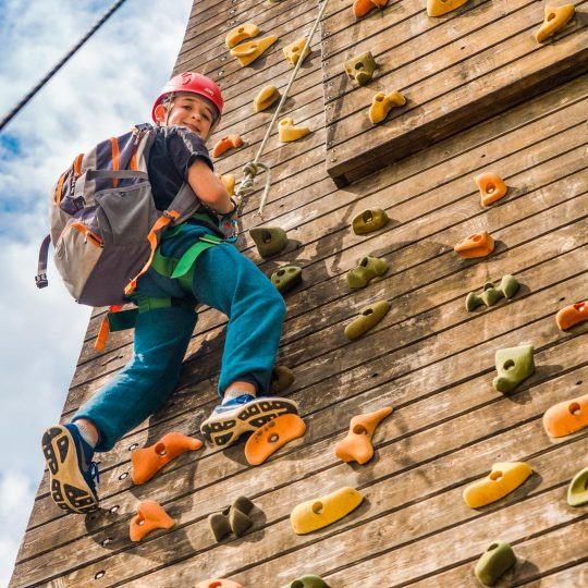 Boy on rock climbing wall with backpack