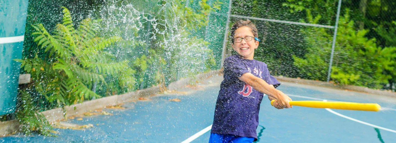 Boy hitting water balloon with bat
