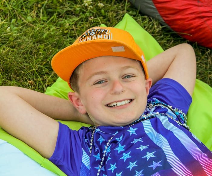 Boy relaxing on blanket on grass