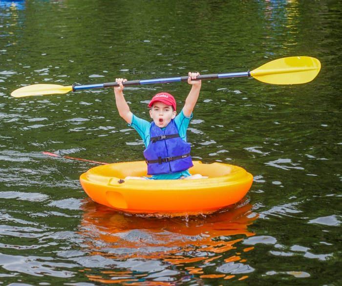 Boy in boat on lake holding oar overhead