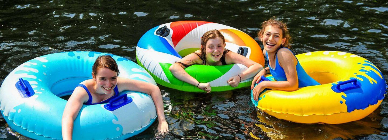 Campers on innertubes in lake