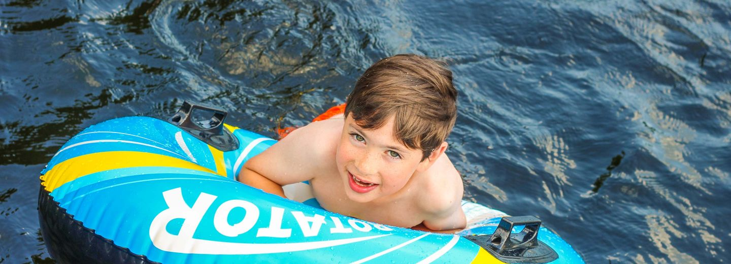 Boy camper in water on inflatable raft
